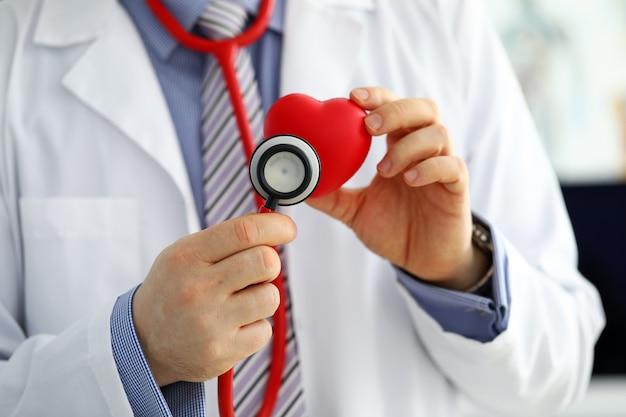 Médico de medicina masculina segurando um coração vermelho e colocando a cabeça do estetoscópio perto dele closeup. assistência médica, cardiologia, cuidados, saúde, profilaxia, prevenção, seguro, cirurgia e, reanimação, conceito