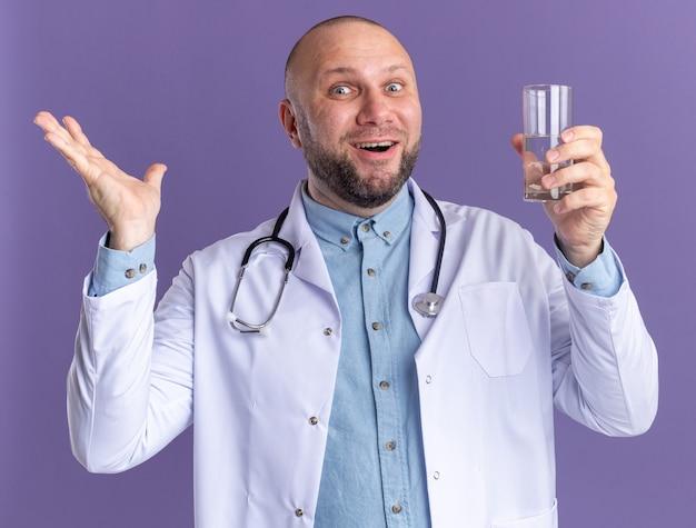 Médico de meia-idade impressionado, vestindo túnica médica e estetoscópio segurando um copo d'água, mostrando a mão vazia isolada na parede roxa