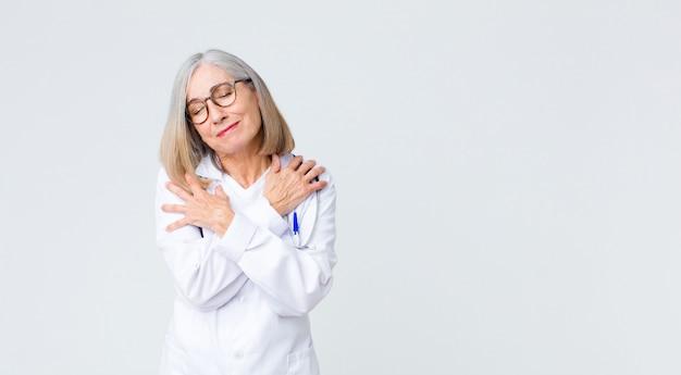 Médico de meia-idade se sentindo apaixonado, sorrindo, abraçando e se abraçando, ficando solteiro, sendo egoísta e egocêntrico