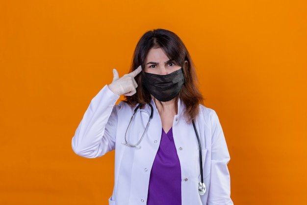 Médico de meia idade vestindo jaleco branco com máscara facial protetora preta e com estetoscópio apontando o templo com o dedo