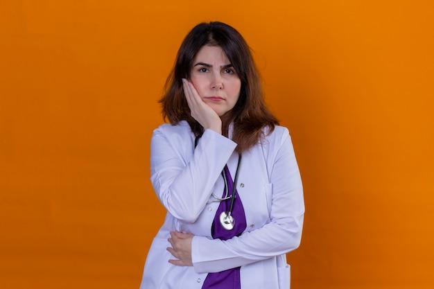 Médico de meia idade vestindo jaleco branco e com estetoscópio cético e expressão de desaprovação nervosa no rosto com a mão na bochecha ao longo da parede laranja