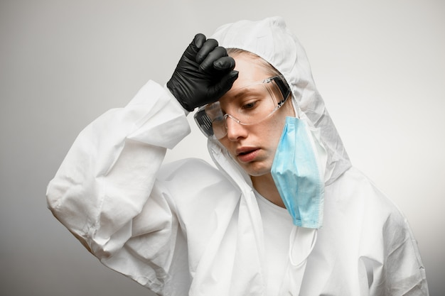 Médico de mulher cansada em roupas de proteção médica com máscara médica removida