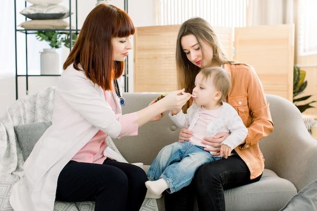 Médico de mulher em casa no jaleco branco examina o bebê pequeno em casa ou na clínica. parece terapeuta médico gentil dá xarope para tosse