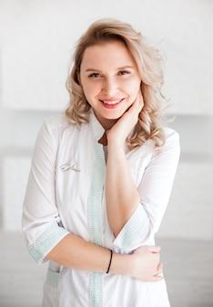 Médico de mulher jovem e bonita posando em vestido branco de médico.