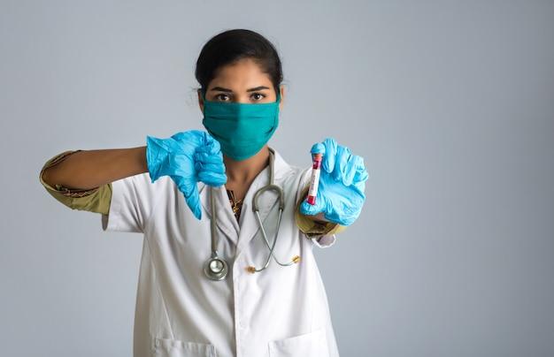 Médico de mulher mostrando sinais segurando um tubo de ensaio com amostra de sangue para análise de coronavírus ou 2019-ncov.