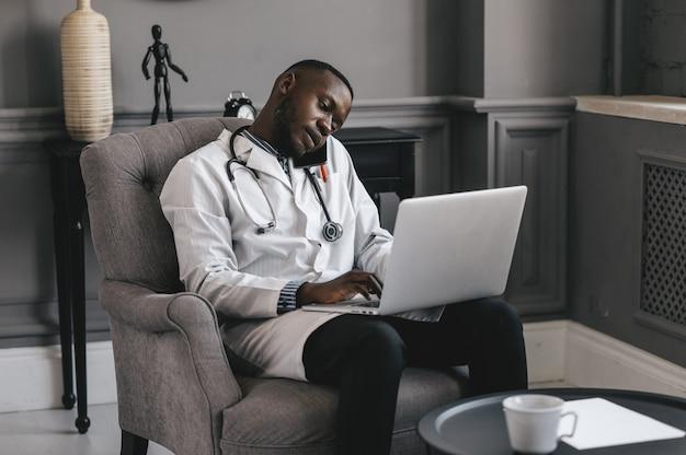 Médico de pele escura falando ao telefone com um laptop. foto de alta qualidade