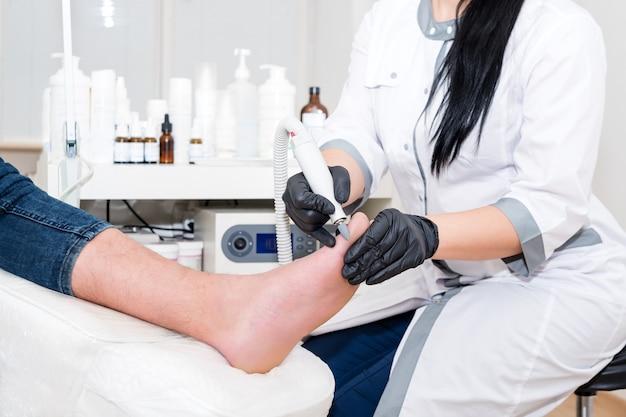 Médico de podologia trata o paciente em clínica moderna