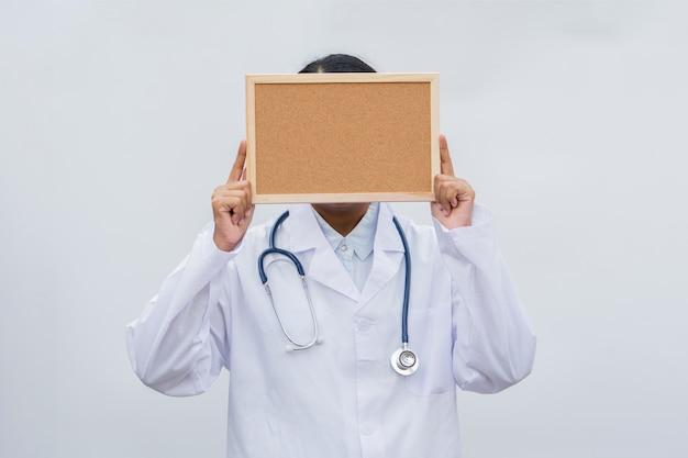 Médico de profissão no jaleco branco sobre fundo branco isolado, com placa em branco branca.
