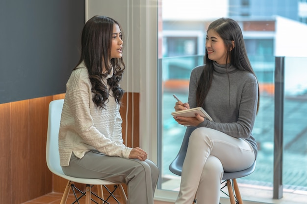 Médico de psicólogo profissional mulher asiática dando a consultar a pacientes do sexo feminino na sala de estar