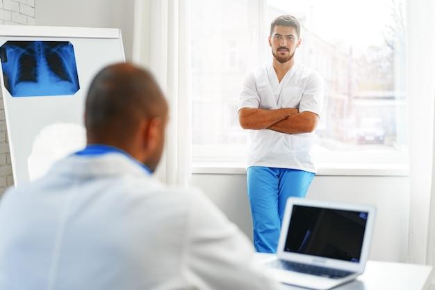 Médico de raça mista, sentado à mesa de trabalho no hospital, close-up