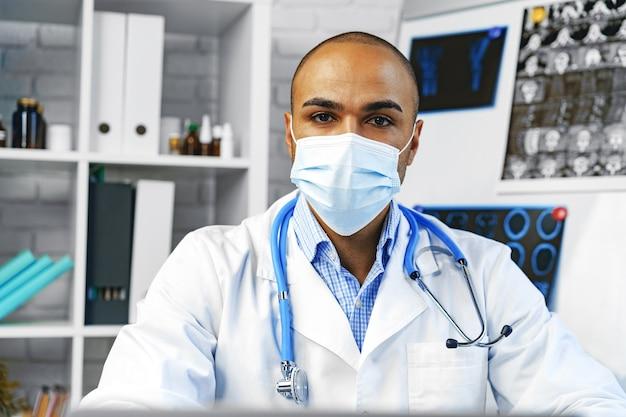 Médico de raça mista sentado à mesa de trabalho no hospital, close-up