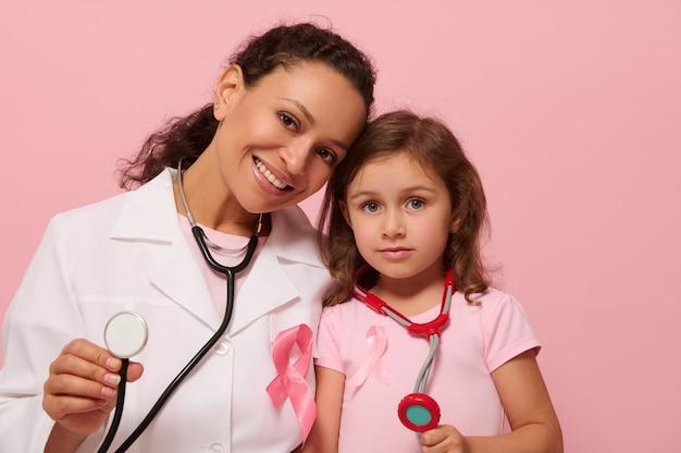 Médico de raça mista sorridente e menina, ambos com fita rosa de conscientização do câncer de mama e estetoscópio em volta do pescoço, mostrando o estetoscópio para a câmera, isolado em um fundo rosa, copie o espaço.