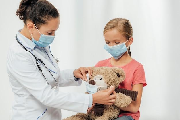 Médico de tiro médio e criança usando máscaras
