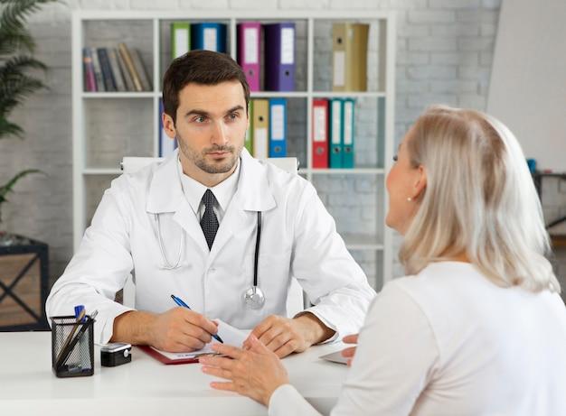Médico de tiro médio falando com mulher