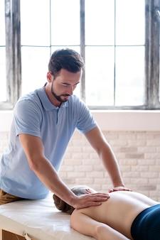 Médico de tiro médio massageando as costas
