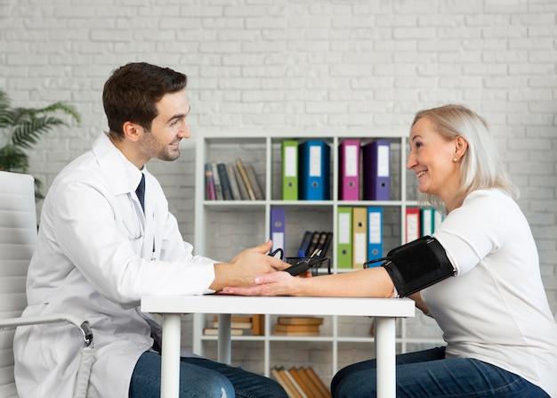 Médico de tiro médio medindo a pressão arterial do paciente