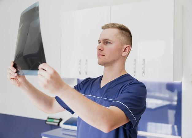 Médico de tiro médio, olhando para a radiografia do animal