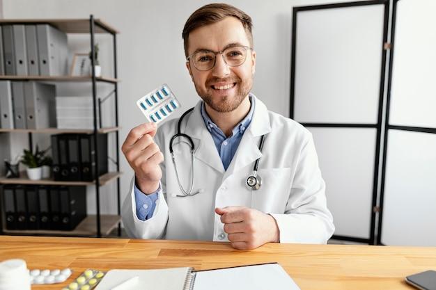 Médico de tiro médio segurando bolha de comprimidos