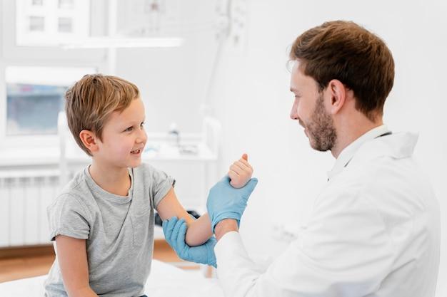 Médico de tiro médio segurando o braço de uma criança