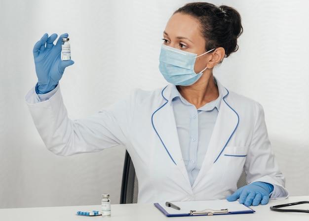 Médico de tiro médio segurando o frasco