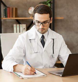 Médico de tiro médio tomando notas