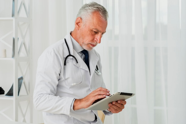 Médico de tiro médio usando tablet