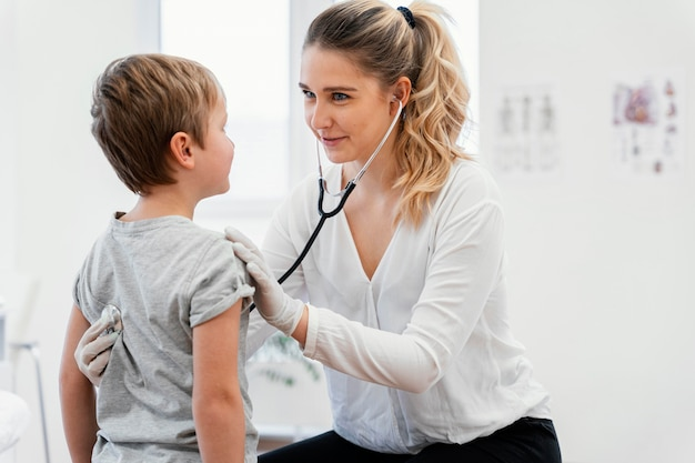 Médico de tiro médio verificando criança