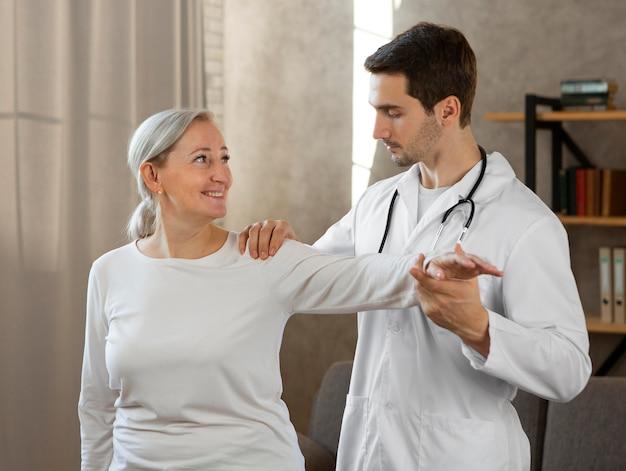 Médico de tiro médio verificando mulher
