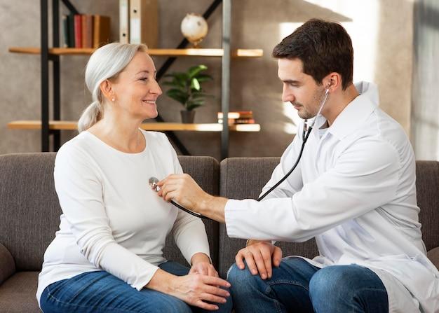 Médico de tiro médio verificando os batimentos cardíacos