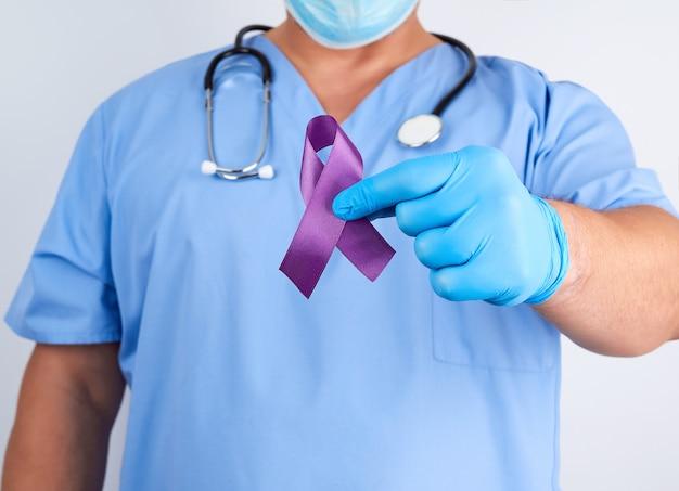 Médico de uniforme azul e luvas de látex segura uma fita roxa como símbolo de pesquisa e controle de doenças