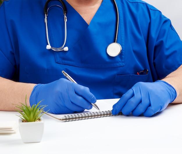 Médico de uniforme azul sentado a uma mesa branca e escrevendo em um caderno de papel