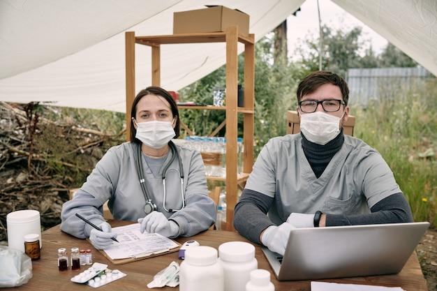 Médico de uniforme com duas luvas trabalhando à mesa