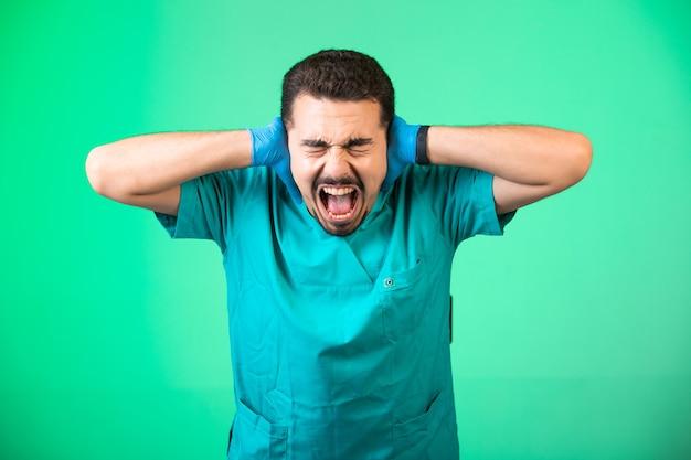 Médico de uniforme e máscara de mão cobrindo as orelhas e tendo choque emocional, sobre fundo verde.