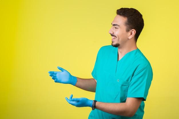 Médico de uniforme e máscara de mão parando e perguntando.