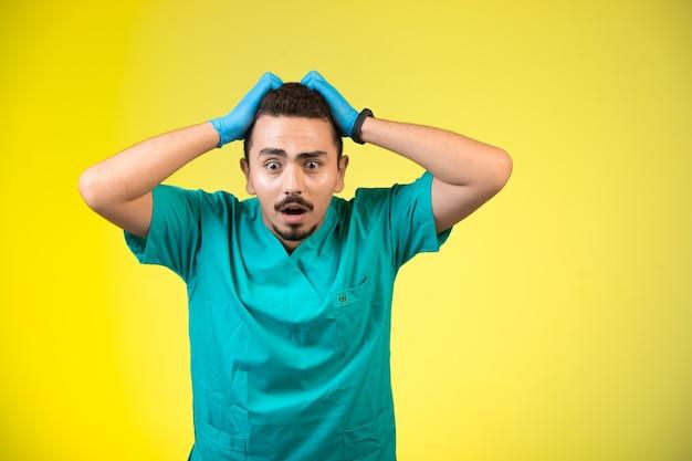 Médico de uniforme verde e máscara de mão frustrado e confuso.
