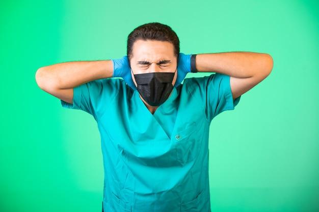 Médico de uniforme verde e máscara facial cobrindo as orelhas.