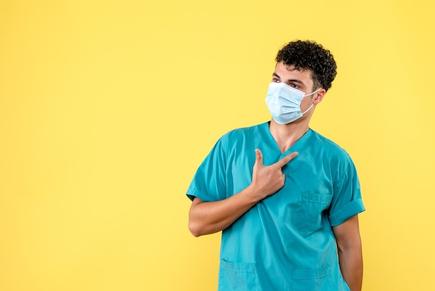 Médico de visão frontal o médico com máscara encoraja as pessoas a observar as regras de higiene