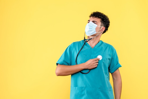 Médico de visão frontal o médico com máscara verifica seu coração