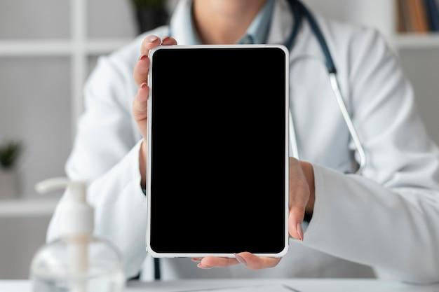 Médico de vista frontal segurando o tablet