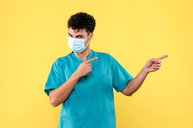 Médico de vista frontal; um médico na máscara aponta para o lado
