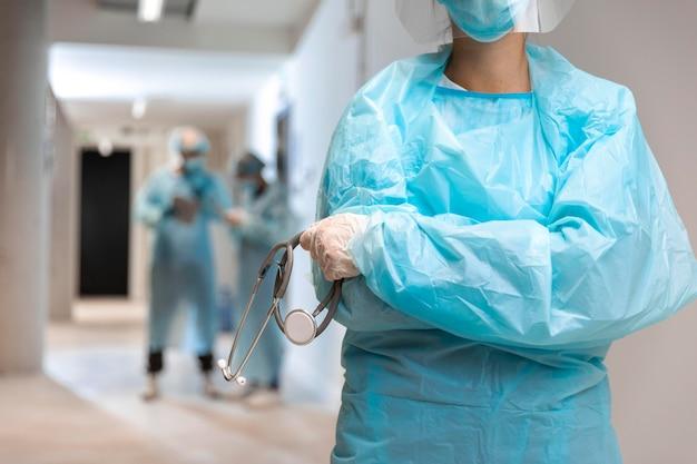Médico de vista frontal usando roupas de proteção no hospital