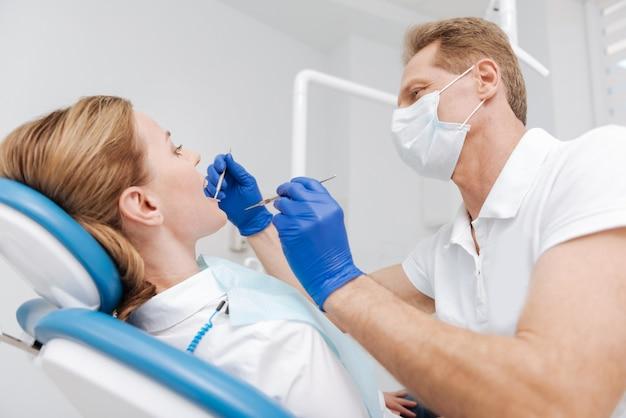 Médico dedicado e atencioso que emprega ferramentas profissionais, enquanto dá uma consulta à sua paciente e examina os dentes