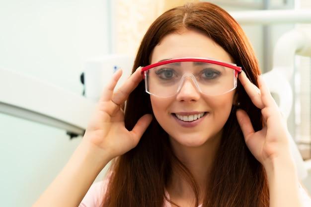 Médico dentista em carrinhos no contexto do consultório odontológico. médico jovem e bonita mulher em roupas médicas e óculos de proteção.