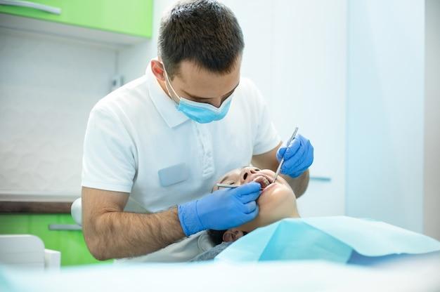 Médico dentista examina a boca de uma jovem em consultório odontológico