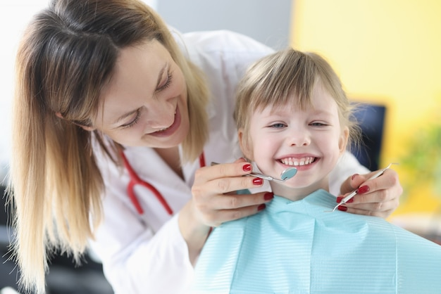Médico dentista examina os dentes da menina