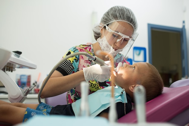 Médico dentista infantil trata os dentes com diferentes dispositivos