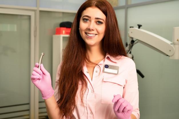 Médico dentista no consultório odontológico. médico jovem e bela mulher em roupas médicas e óculos de proteção, possui uma ferramenta dental profissional nas mãos dela. sorridente.