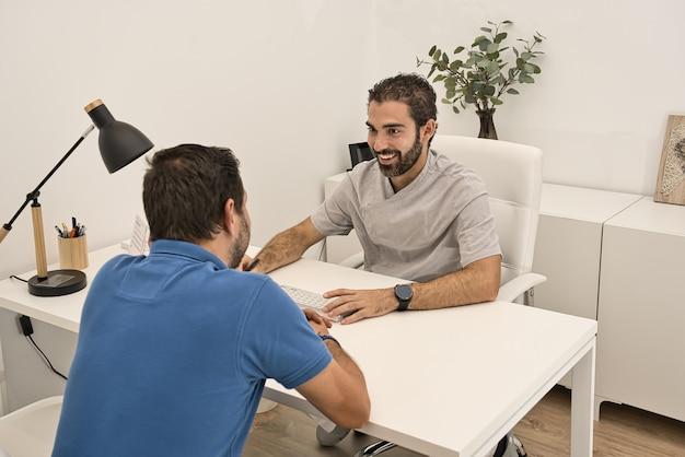 Médico dentista, reunido em seu escritório e sentado em uma mesa, atende com um sorriso a um cliente vestindo uma camisa polo azul em uma clínica odontológica moderna.