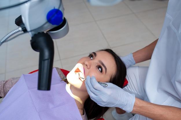 Médico dentista trata os dentes de uma bela jovem paciente a mulher na recepção do dentista médico dentista trata o dente