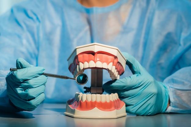 Médico dentista usando luvas azuis e uma máscara segurando um modelo dentário
